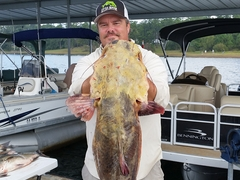 Man with fish and two charter boats Little River Guide Service Clarks Hill Lake GA Lake Strom Thurmond SC